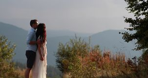 Love in the mountains. Man hugs woman from behind tender and kisses her watching sunset over the mountains on a hill