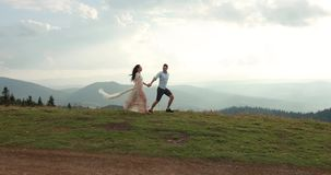 Love in the mountains. Man and woiman run along the road to the horizon somewhere on the hill while sun shines over them.  stock footage