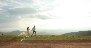 Love in the mountains. Man and woiman run along the road to the horizon somewhere on the hill while sun shines over them.  stock video footage