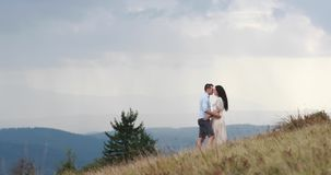 Love in the mountains. Man and woman hold each other hands standing on the hill and watching rain far away on the. Horizon stock video footage