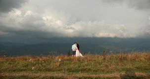 Love in the mountains. Man and woman hold each other hands standing on the hill and watching rain far away on the. Horizon stock footage