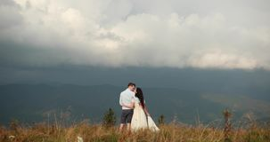 Love in the mountains. Man and woman hold each other hands standing on the hill and watching rain far away on the. Horizon stock video