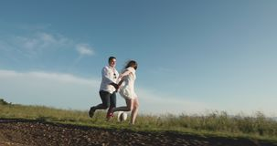 Cheerful young couple hiking in summer on mountain top. Love in the mountains. Man and woman run along the road to the. Love in the mountains. Man and woman run stock video footage