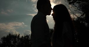 Love in the mountains. Solhouettes of man and woman kissing in the rays of evening sun.  stock video footage