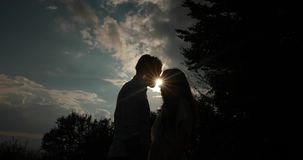 Love in the mountains. Solhouettes of man and woman kissing in the rays of evening sun.  stock video