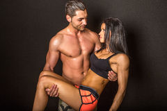 Muscular man carrying athletic woman Royalty Free Stock Image