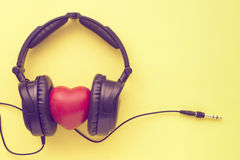 Love music concept. Black headphones with red heart, wires and socket on yellow background Royalty Free Stock Photography