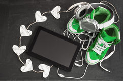 Love for music concept. Green sneakers, headphones, tablet and h Stock Images