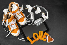 Love for music concept.Orange sneakers, headphones, tablet and h Royalty Free Stock Images