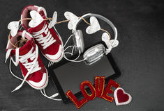 Love for music concept. Red sneakers, headphones, tablet and hea Royalty Free Stock Photo