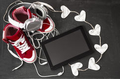 Love for music concept. Red sneakers, headphones, tablet and hea Stock Photos