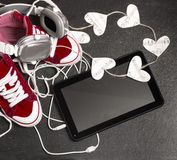 Love for music concept.Red sneakers, headphones, tablet,hearts. Stock Photo