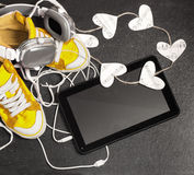 Love for music concept. Yellow sneakers, headphones, tablet,hear Royalty Free Stock Photography