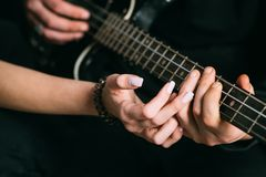 We love music. Couple in love play duets. Male and female hands play the electric guitar. Couple of guitar players. Couple of musicians enjoy playing music royalty free stock image