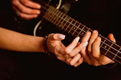We love music. Couple in love play duets. Male and female hands play the electric guitar. Couple of guitar players. Couple of musicians enjoy playing music stock images