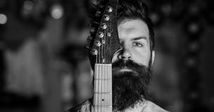 Love Music. Musician, artist on pensive, calm face and guitar neck. Man with beard and mustache covers half of face with guitar neck, close up. Man in music royalty free stock photography