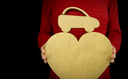 Love my car. Woman holding gold love heart and car Royalty Free Stock Photos