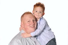 Love My Dad. Young redheaded boy smiling and hugging his father Royalty Free Stock Photos