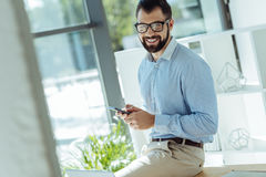 Charming man with smartphone in hands posing for camera Stock Photo
