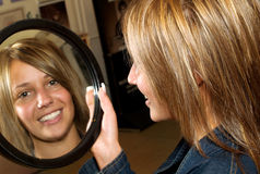 Love my new hair-style!. Girl with new hair-style looking herself in the mirror Stock Image