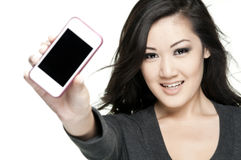 Love my phone. Beautiful asian teenager holding her phone toward camera, white background, phone is soft focus Royalty Free Stock Photography