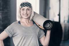 Female personal trainer holding a yoga mat on her shoulder. Love my work. Pleasant female personal trainer standing in the gym and holding a yoga mat on her Stock Photo