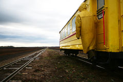 Love my work. Yellow coated man hanging on carriage Stock Photo