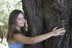 Love nature. Beautiful young girl hugging a tree royalty free stock photography