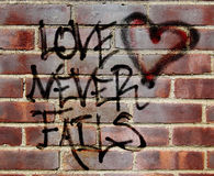 Love never fails graffiti. Original graffiti illustration combined with a photograph of a brick wall Royalty Free Stock Photo