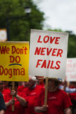 Love never fails. A man walks in the gay pride parade in Des Moines, Iowa holding a sign that promotes love stock photo