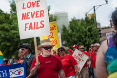 Love Never Fails. A man walks in the gay pride parade and holds a sign that supports marriage equality Stock Photography