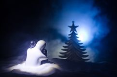 Love New Year concept. Girl and boy ceramic figures hugs each other, standing on the white snow and colored heart and Christmas tr. Ee on blurred dark background Stock Images