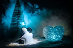 Love New Year concept. Girl and boy ceramic figures hugs each other, standing on the white snow and colored heart and Christmas tr. Ee on blurred dark background Stock Photos