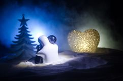 Love New Year concept. Girl and boy ceramic figures hugs each other, standing on the white snow and colored heart and Christmas tr. Ee on blurred dark background Stock Image