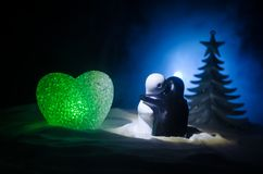 Love New Year concept. Girl and boy ceramic figures hugs each other, standing on the white snow and colored heart and Christmas tr. Ee on blurred dark background Royalty Free Stock Images