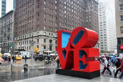 Love, New York. NEW YORK, USA - JUNE 7, 2013: People walk past Love sculpture in rain in New York. The famous monument by Robert Indiana is located on 6th Avenue royalty free stock photography