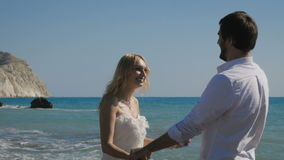 In love newlyweds embraces on the shore of ocean. Portrait of a man straightens a girl`s hair. Newlyweds hold hands and look at each other. A charming woman in a stock footage