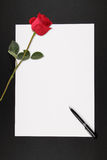 Love Note. A blank piece of paper with a stalk of rose and pen, with copy space ready for someone to write a love note, against a dark background Royalty Free Stock Image