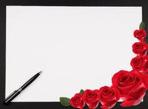 Love Note 2. A blank piece of paper with pen and rose border with copy space suitable for a love note, against a dark background stock image