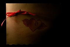 Love Note. A picture of the front of a love note with a red bow in the upper left and a winged heart in the center Royalty Free Stock Images