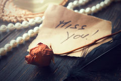 Love note on an old parchment paper. With words miss you on it, decorated with old withered rose Royalty Free Stock Photos