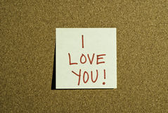 Love Note Post it. A post it love note that says I Love You in red marker on a cork board Royalty Free Stock Images