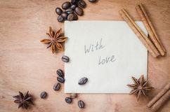 With love note and spices, sticks of cinnamon and anise star on wooden background. Royalty Free Stock Photo