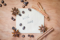 With love note and spices, sticks of cinnamon and anise star on wooden background. Royalty Free Stock Images