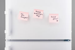 Love notes on light pink sticky paper on white refrigerator. See you tonight, happy valentines day, love you notes on light pink sticky paper on white Stock Image