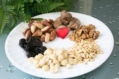 Love Nuts and dried fruits. Nuts and dried fruits mix on the white plate Royalty Free Stock Images