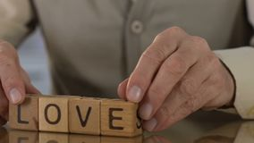 Love, old man making word of wooden cubes, caring father and grandpa, family