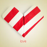Love. An origami heart and the word love on a beige background with a retro effect Royalty Free Stock Image