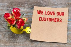 We love our customers -  inscription on vintage sheet of paper a. Nd bouquet of roses Stock Photo