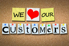 We love our customers on wooden cork billboard with colored pins. We love our customers on wooden cork board with colored paper pins Stock Images